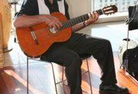 Roy taking up guitar